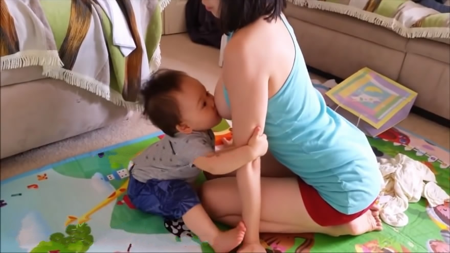 在家带两个孩子的哺乳期年轻漂亮妈妈如何给宝贝喂奶的大大凸起的