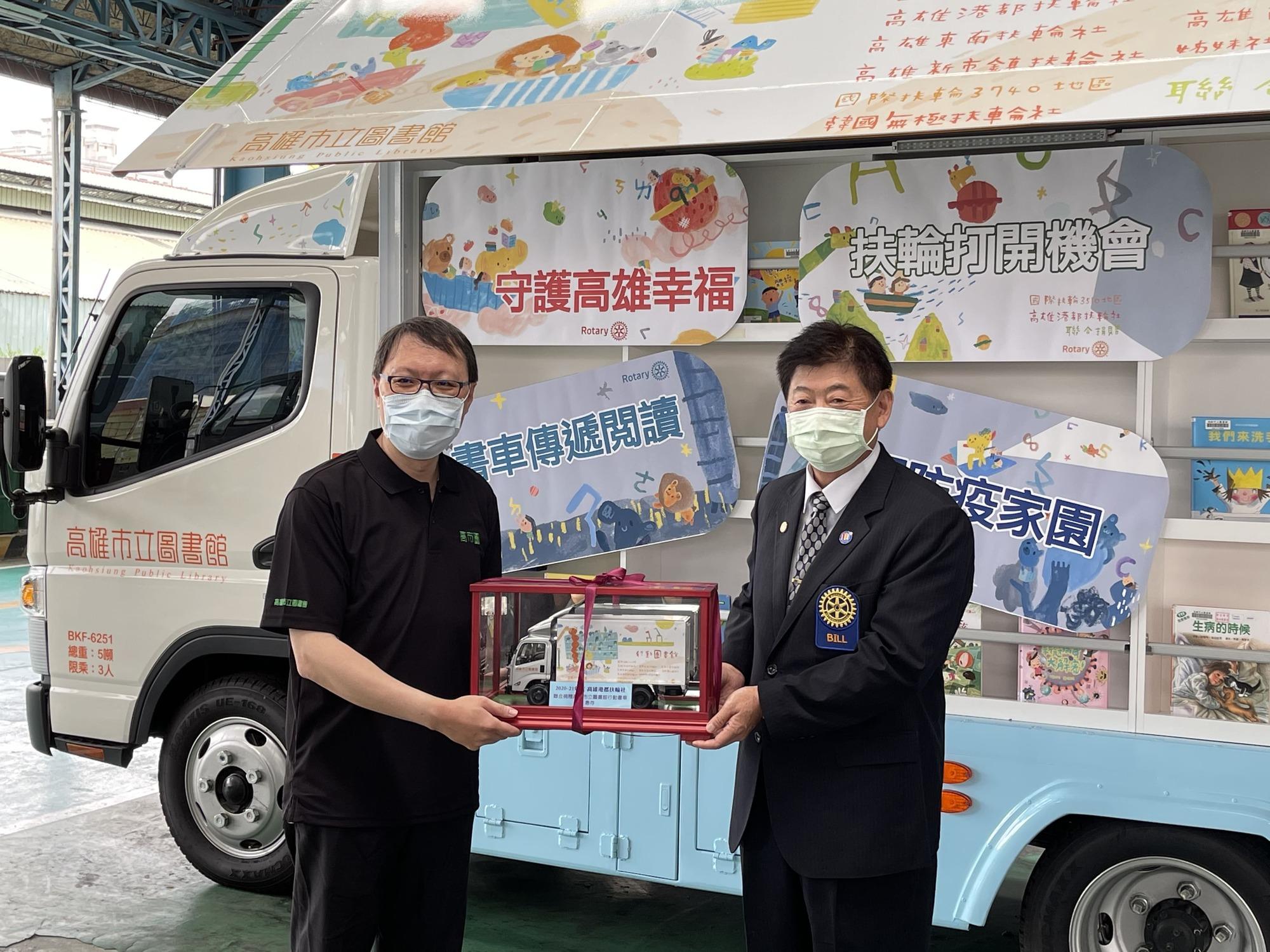 高市圖代理館長林奕成(左)贈行動書車模型予港都扶輪社社長崔斌弘(右)表示謝意